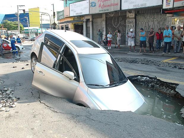 Um carro caiu em uma cratera na Rua Rua Elza Fagundes Teles, no Jardim Roberto, em Osasco, na Grande São Paulo, na manhã desta quinta-feira (6). Segundo a prefeitura do município, uma adutora da Companhia de Saneamento Básico do Estado de São Paulo (Sabesp) rompeu e formou a cratera. Técnicos da Secretaria de Serviços e Obras foram acionados para acompanhar a ocorrência. Até as 10h50, não havia informações de feridos. (Foto: Renato Silvestre/Estadão Conteúdo)