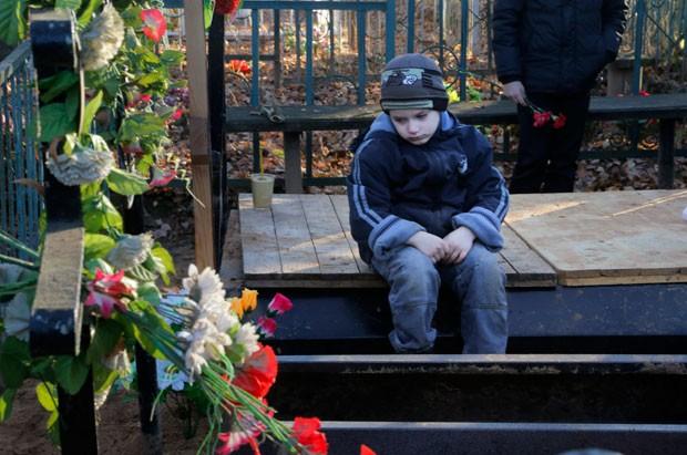 Mikhail, neto de Nina Lushchenko, uma das vítimas da queda do voo de um avião russo na península do Sinai, no funeral da avó (Foto: Ivan Sekretarev/AP)