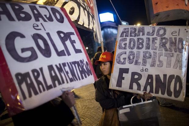 Manifestantes protestam em apoio ao presidente Fernando Lugo na noite de sexta-feira (22) em Assunção (Foto: AFP)
