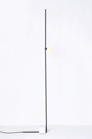 Uma fina haste de alumínio se equilibra por um bloco de mármore e ganha um difusor de vidro soprado com módulo de LED. Luminária Adobe, do designer Guilherme Wentz (Foto: Lorena Dini / Divulgação)