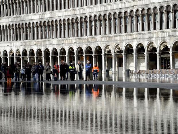 Turistas na Praça de São Marcos inundada, em Veneza (Foto: Olivier Morin/AFP)
