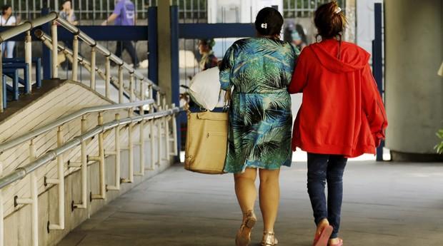 Menor que foi vítima de estupro coletivo deixa o Hospital Souza Aguiar, acompanhada da mãe.  (Foto: Gabriel de Paiva/ Agência O Globo)