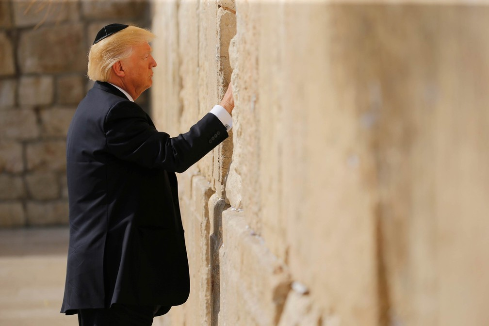 Donald Trump coloca um bilhete entre rochas do Muro das Lamentações, local de orações do Judaísmo, em Jerusalém, Israel (Foto: Jonathan Ernst/Reuters)