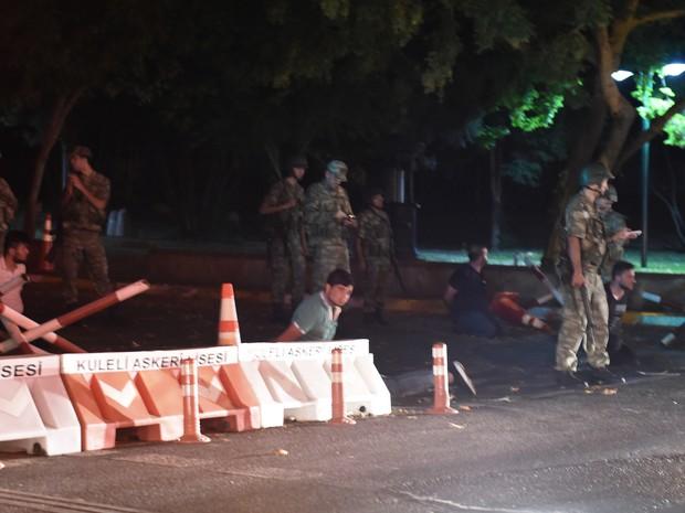 Agentes de segurança da Turquia detem policiais ao lado da estrada, em Istambul (Foto: Bulent Kilic / AFP)