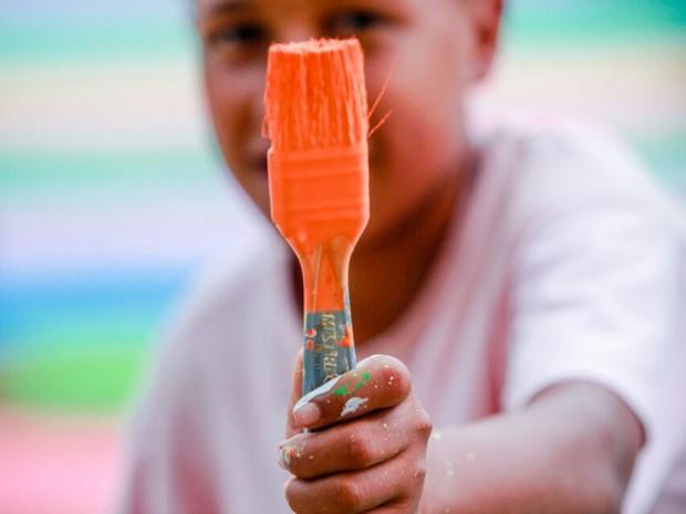 O projeto reune cerca de 60 crianças para pintar quadros, ruas e paredes (Foto: Divulgação/Bruno Itan)