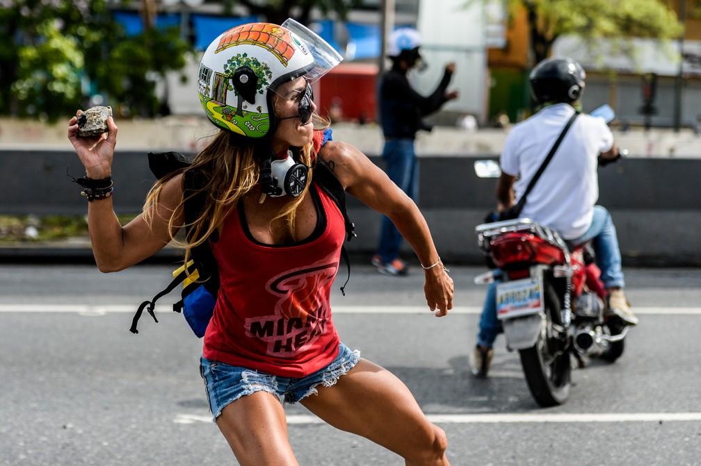 Manifestante joga pedra em protesto no dia 1º de maio em Caracas (Foto: Federico Parra/AFP)