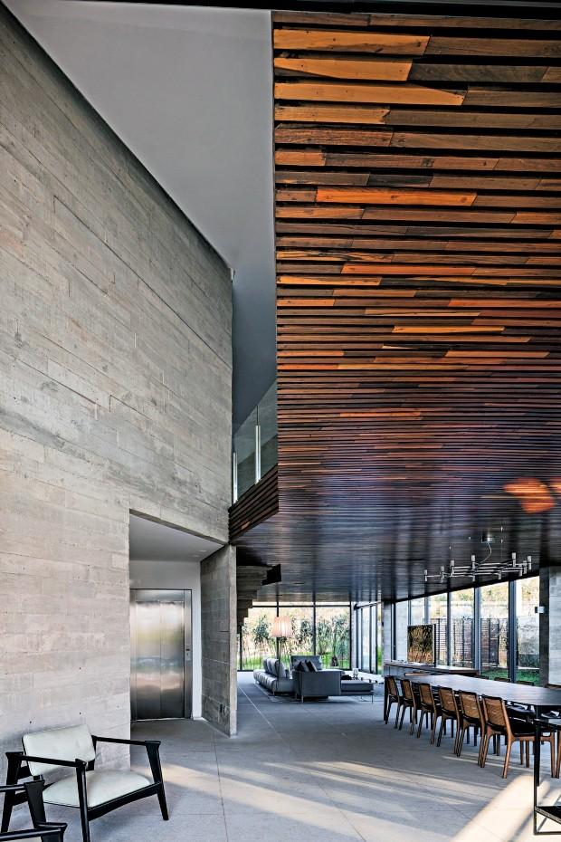 Integração. Além de escadas, há o elevador interligando os três pavimentos. O desenho das marcas das réguas de madeira na parede de concreto se repete no revestimento de ipê do volume suspenso (Foto: Leonardo Finotti e Daniel Mansur / Divulgação)