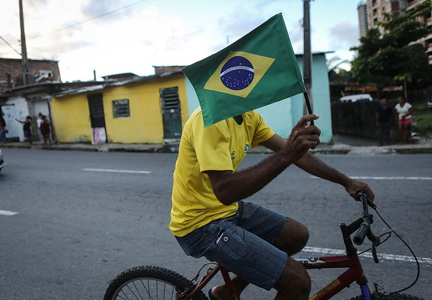 Homem carrega uma bandeira do Brasil (Foto: Mario Tama/Getty Images)