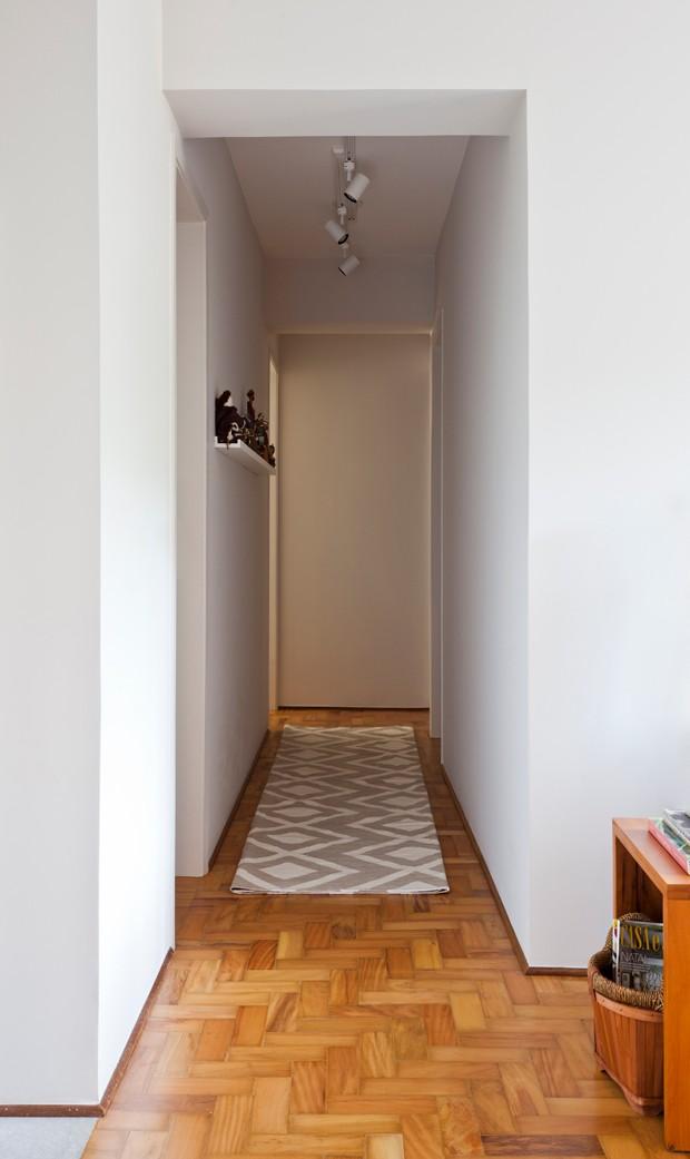 O corredor não precisa ser apenas para circulação. Nesse projeto, ele ganha ares de galeria de arte com canaletas para expor quadros e gravuras. Tapete by Kamy (Foto: Maira Acayaba)