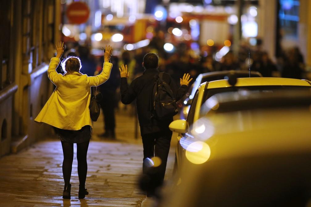 Pessoas levantam as mãos durante operação policial em rua próximas à avenida Champs Elysees, em Paris, onde houve um tiroteio na noite desta quinta-feira (20) (Foto: REUTERS/Benoit Tessier)