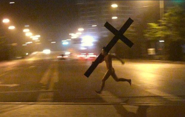 Foto de homem nu correndo com um crucifixo gigante virou viral na internet (Foto: Reprodução/Weibo)