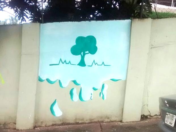 Após pintar, adolescente desenhou uma árvore no muro da escola ' (Foto: Arquivo Pessoal)