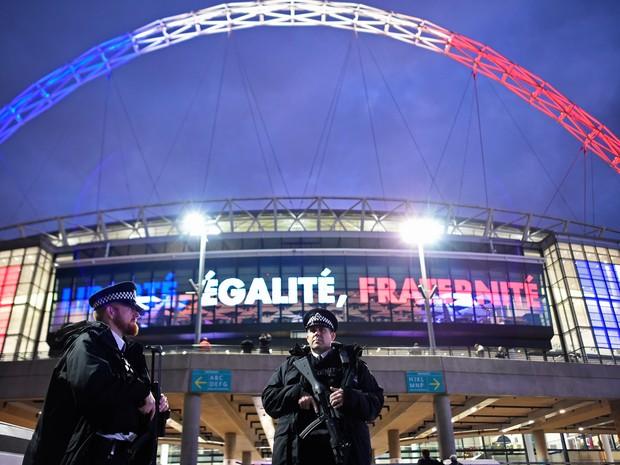 Policiais armados são vistos em frente ao estádio Wembley, em Londres, antes do amistoso entre Inglaterra e França; Ao fundo é possível ver o estádio iluminado com as cores da bandeira francesa e o lema 'Liberdade, Igualdade, Fraternidade'  (Foto: Dylan Martinez/Livepic/Reuters)