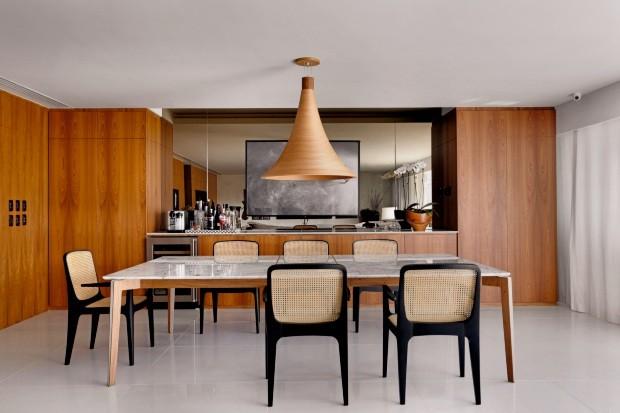 O freijó está também presente, como no aparador desenhado pelos arquitetos. Acima, diante de um espelho, foto de Sérgio Machado, na Almacén Galeria. A mesa, com tampo de mármore Carrara, e as cadeiras são de Jader Almeida (Foto: Denilson Machado / MCA Estúdio)