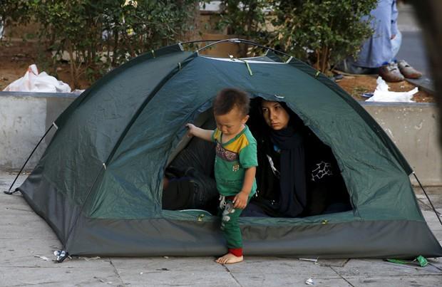 Menino afegão sai de barraca onde passou a noite na Praça Victoria no Centro de Atenas, na Grécia (Foto: Paul Hanna/Reuters)