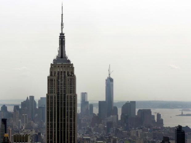O Empire State Building, que tem 1.454 pés de altura (à esq.), é visto ao lado do One World Trade Center, que tem 1.776 pés de altura (centro), com a Estátua da Liberdade ao fundo, à direita. A foto foi tirada da plataforma de observação do Rockefeller Ce (Foto: Richard Drew/AP)