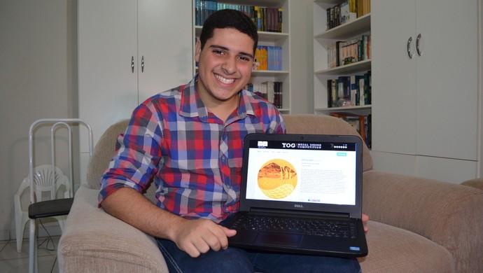 Gabriel com a imagem de sua medalha no site (Foto: Magda Oliveira)