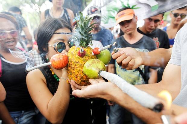 Participante fuma maconha em um 'cachimbo' improvisado feito com abacaxi e outras frutas (Foto: Fredy Builes/Reuters)