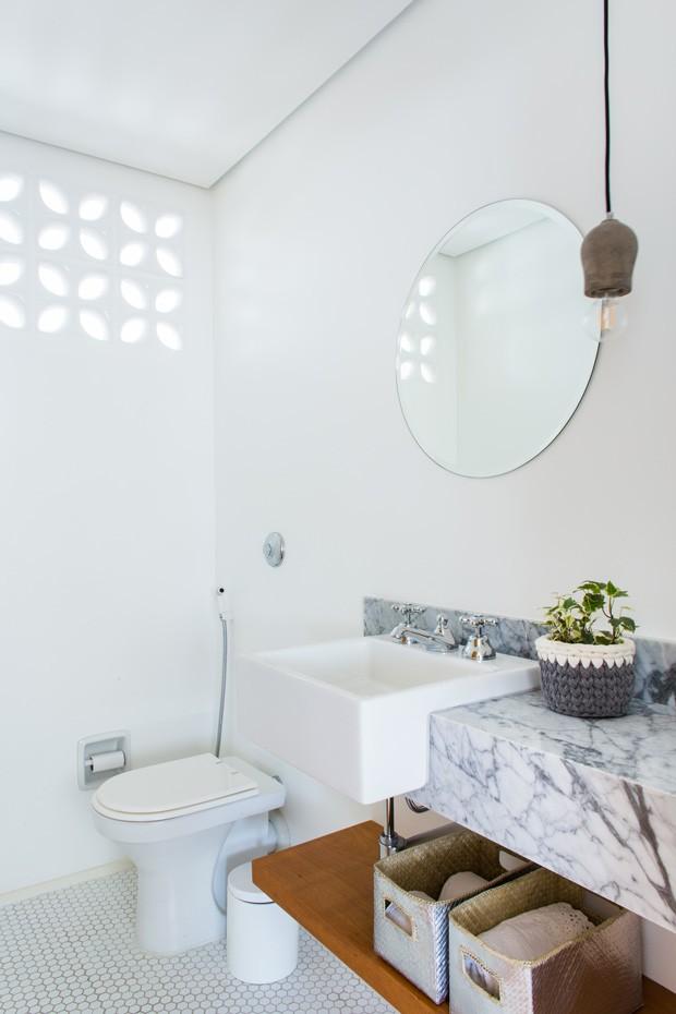 O lavabo teve que ser criado do zero em um antigo quarto. A bancada da pia é de mármore carraca, da marca Deca. A cuba e a torneira também são da mesma marca. Já a luminária, pendente em concreto, é da marca Yamamura (Foto: Estúdio Pulpo)