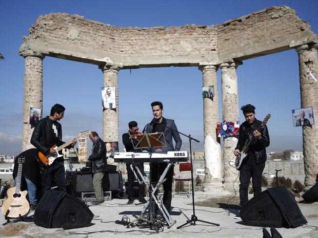 Uma banda afegã toca entre ruínas do palácio Darul Aman em Cabul, durante a campanha 'Mil Sorrisos por Paz', da ONG antiviolência NVWO (Non-Violent World Organization) (Foto: Ahmad Masood/Reuters)