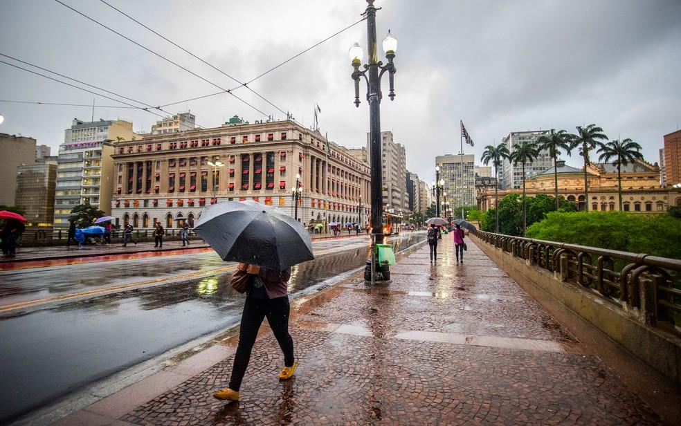 Pedestre enfrenta garoa no fim nas imediações do Viaduto do Chá, no centro de São Paulo (Foto: Cris Faga/Fox Press Photo/Estadão Conteúdo)