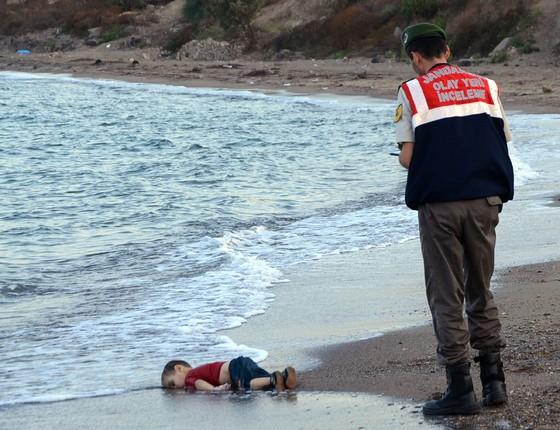 Oficial encontra corpo sem vida de uma criança refugiada, que morreu enquanto seguia para ilha grega de Kos (Foto: AP Photo/DHA)