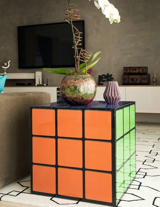 A mesa de cubo mágico dá um ar de descontração. O cimento queimado nas paredes empresta toque rústico e moderno aos ambientes (Foto: Marcelo Tabach/Ed. Globo)