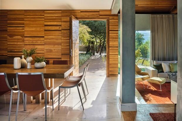Uma passarela de madeira de demolição cruza o jardim para dar acesso à casa. De um lado, ficam a sala de jantar e a cozinha; do outro, dois degraus abaixo, a sala de estar coma poltrona Womb de Eero Saarinen, da São Romão (Foto: Jomar Bragança / Divulgação)