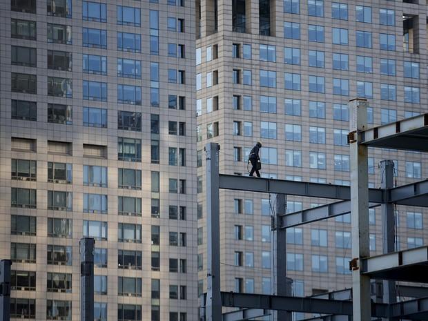 Operário caminha sobre estrutura de prédio em construção em Pequim (Foto: Kim Kyung-Hoon/Reuters)