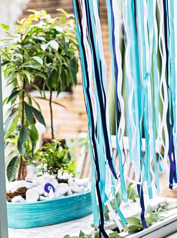 Fitas em vários tons de azul dão as boas-vindas aos convidados na entrada. Ao fundo, arranjo com seixos, plantas e olho grego na peça de cerâmica da Olaria Paulistana (Foto: Elisa Correa/Editora Globo)