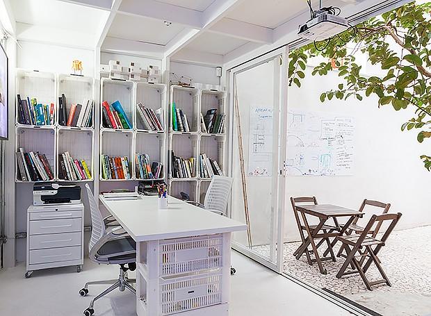 Área reservada: para reuniões com clientes ou brainstorms, a sala nos fundos do sobrado tem estante feita com caixotes plásticos, também utilizados para a base da mesa (Foto:  Lufe Gomes/ Editora Globo)