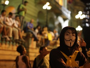 Manifestante com máscara do filme 'V de Vingança' e flores na mão participa de protesto no Centro do Rio (Foto: Rodrigo Gorosito/G1)