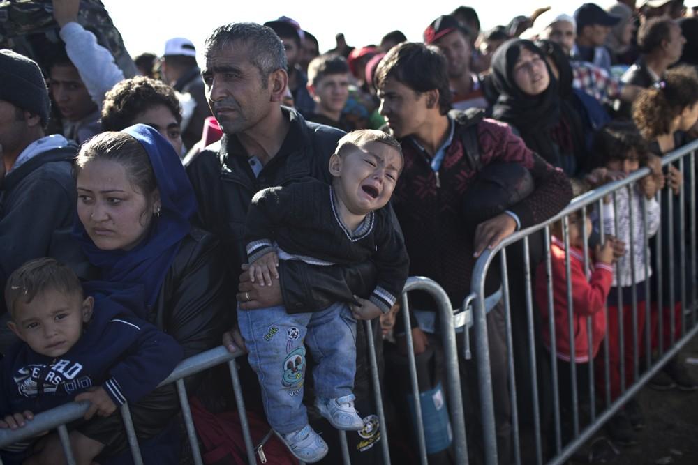 Uma criança chora nos braços do pai enquanto um grupo de refugiados espera ser atendido em um centro de acolhimento em Opatovac, na Croácia (Foto: AP Photo/Marko Drobnjakovic)