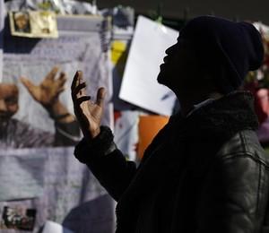 Homem reza em frente a um muro  com mensagens na entrada do hospital onde o ex-presidente sul-africano Nelson Mandela está internado, em Pretória, África do Sul (Foto: AP Photo/Markus Schreiber)