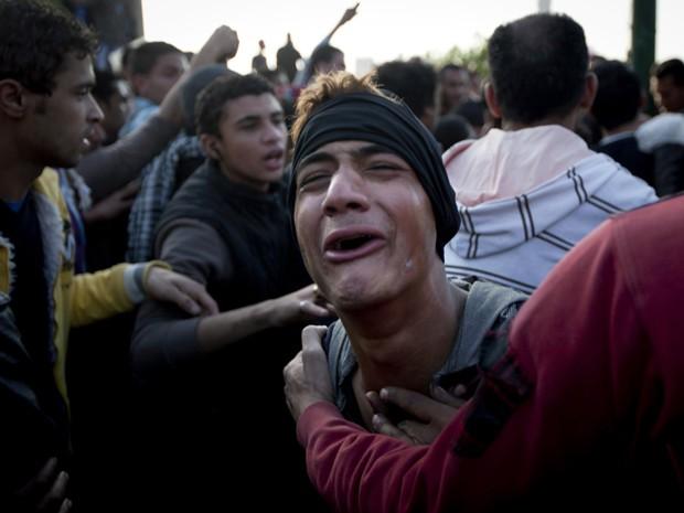 Jovem chora por colega morto em confronto com a polícia no Cairo neste sábado (9) (Foto: Nasser Nasser/AP)