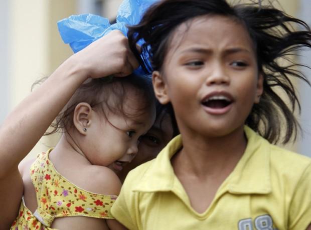 Crianças correm para abrigo na região costeira para se abrigar do tufão Hagupit, em Manila  (Foto: Reuters)