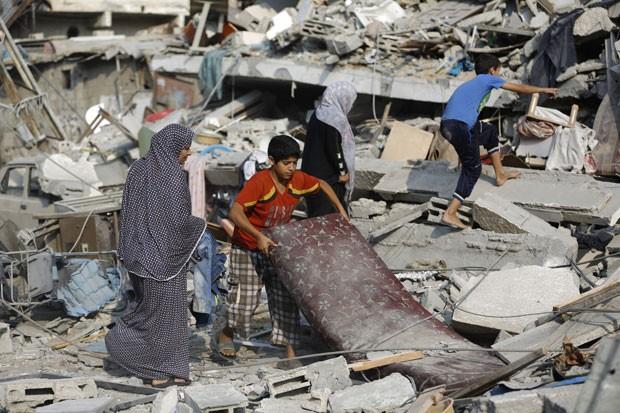 Menino palestino carrega colchão retirado dos escombros do apartamento de sua família, bombardeado nesta terça-feira (22) no centro da cidade de Gaza (Foto: Mohammed Abed/AFP)