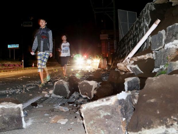 Pessoas caminham perto de destroços após tremor atingir Mashiki, em Kumamoto, no Japão, nesta quinta-feira (14) (Foto: Kyodo News via AP )