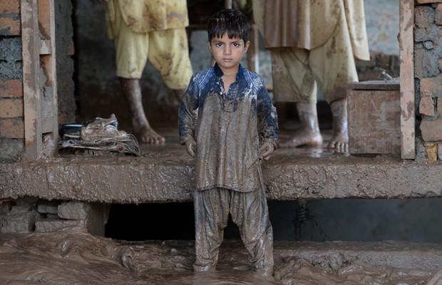 Menino paquistanês em sua casa suja de lama em Rawalpindi, neste sábado (6) (Foto: Farooq Naeem/AFP)