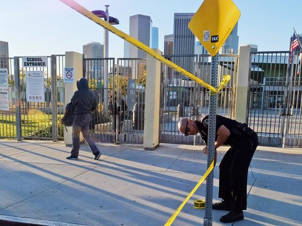 Um policial coloca fita amarela para fechar o perímetro do lado de fora da escola de ensino médio Edward Roybal em Los Angeles, nos EUA. Todas as escolsa da cidade foram fechadas nesta terça-feira (15) após uma ameaça de bomba (Foto: Richard Vogel/AP)