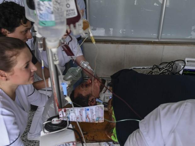 O zagueiro Neto (Hélio Zampier Neto) é levado de maca após chegar à clínica San Juan de Dios em La Ceja, no departamento de Antioquia, na Colômbia (Foto: Luis Acosta/AFP)