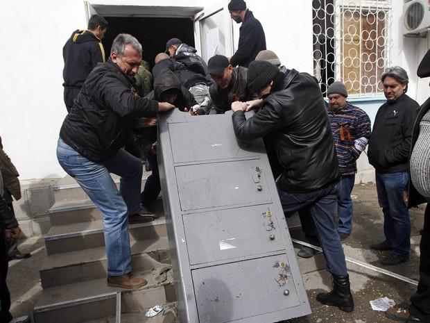 19/3 - Homens retiram um cofre da sede naval ucraniana na Crimeia depois de ter sido tomado por forças pró-russia em Sebastopol (Foto: Vasily Fedosenko/Reuters)