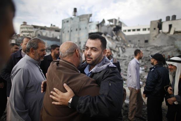 Policial do Hamas é abraçado por palestino ao voltar a posto destruído na Cidade de Gaza nesta quinta-feira (22) (Foto: Reuters)