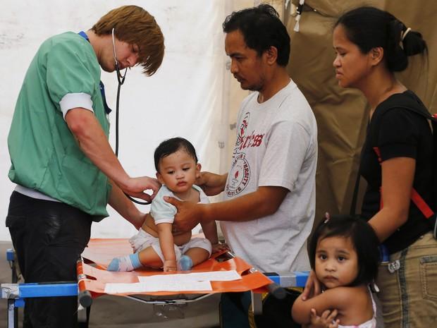 Bebê é atendido em tenda improvisada na cidade de Palo, nas Filipinas (Foto: Wolfgang Rattay/Reuters )