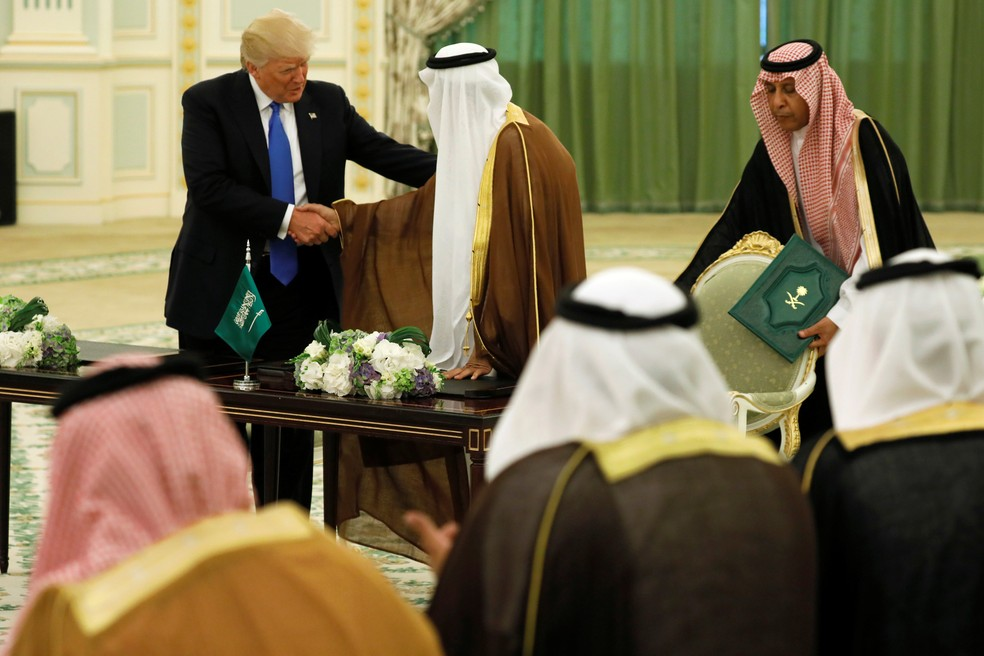 Trump e o rei saudita se cumprimentam após assinar um acordo de segurança (Foto: Jonathan Ernst/Reuters)