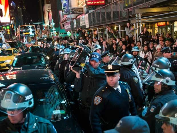 Na Times Square, em Nova York, policiais acompanham manifestação por arquivamento de caso de policial que matou jovem em Ferguson. (Foto: John Minchillo / AP Photo)