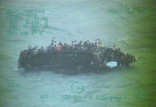 Haitianos se agarram a casco de barco que naufragou próximo às Bahamas nesta terça-feira (26), em imagem divulgada pela Guarda Costeira dos EUA (Foto: AFP)