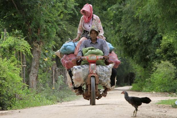 Em setembro de 2012, um casal cambojano foi flagrado andando em uma moto supercarregada com sacos de frutas na vila de Daun You, no Camboja. O casal seguia para o principal mercado da província de Prey Veng, 75 km de Phnom Penh (Foto: Heng Sinith/AP)