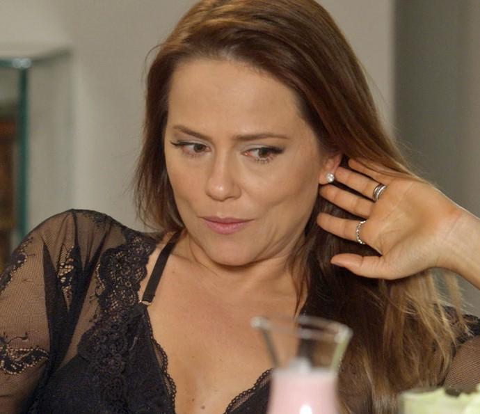 Lili tenta disfarçar ao ouvir a loira dizer que ela pode estar grávida (Foto: TV Globo)