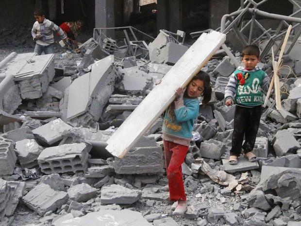 Crianças recolhem pedaços de madeira dentre os destroços de uma escola para surdos-mudos em Raqqa, no leste da Síria. Ativistas afirmam que o local foi destruído por um dos ataques aéreos liderados pelos EUA no combate a terroristas do Estado Islâmico (Foto: Nour Fourat/Reuters)